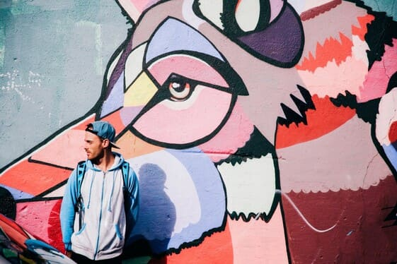 young men standing in front of colorful street art graffiti of a dog t20 pYRYBe
